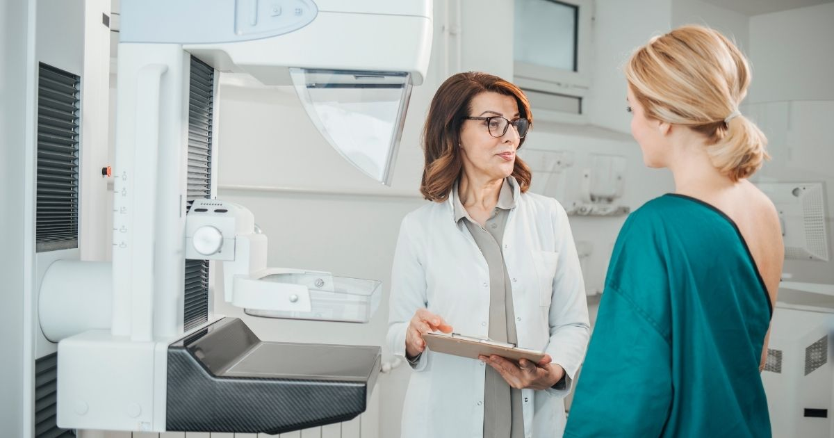 A doctor talks to a woman about to get a mammogram. Doctors have recently recommended women schedule their mammograms before getting their COVID-19 vaccine or 4-6 weeks after to avoid presenting symptoms similar to cancer symptoms on screenings.