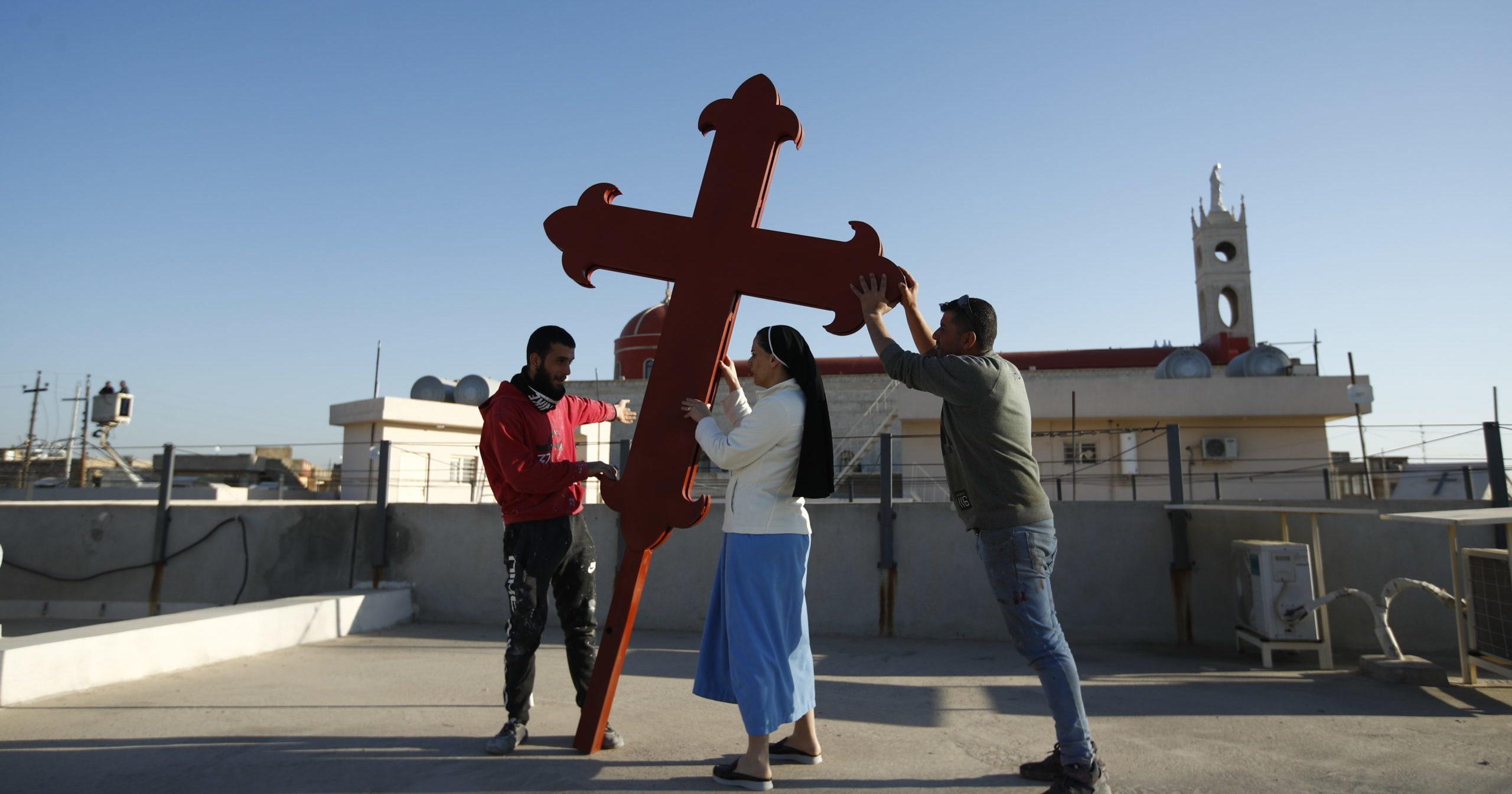 Iraqi Christians place a cross on a church in Qaraqosh, Iraq, on Feb. 22, 2021.