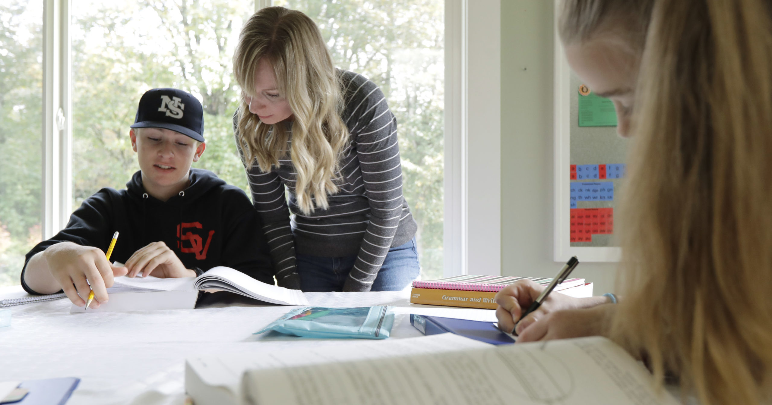 Donya Grant, center, works on a lesson with her son Kemper, 14, as her daughter Rowyn, 11, works at right at their home in Monroe, Washington, on Oct. 9, 2019.