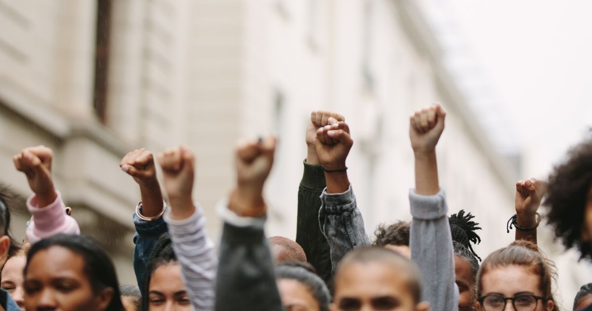 Protesters in a mob are pictured raising their fists in the stock image above.