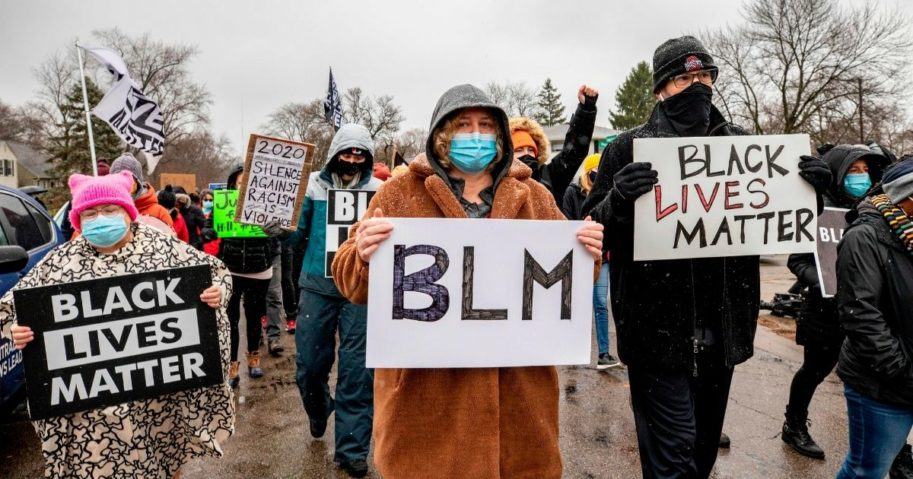 Protesters holding BLM signs march in Columbus, Ohio, on Dec. 24, 2020.