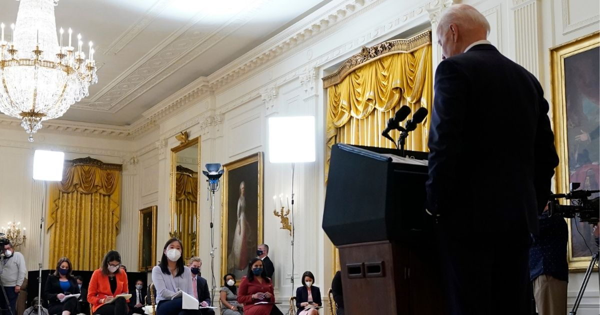 President Joe Biden looks at his notes during his first news conference in the East Room of the White House in Washington on Thursday.