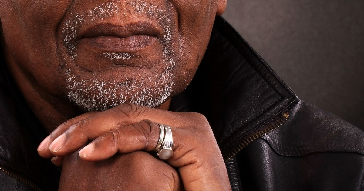 An older black man with his hands clasped.