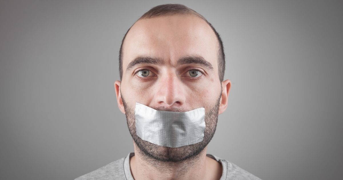 A man with duct tape over his mouth is pictured in the stock image above.