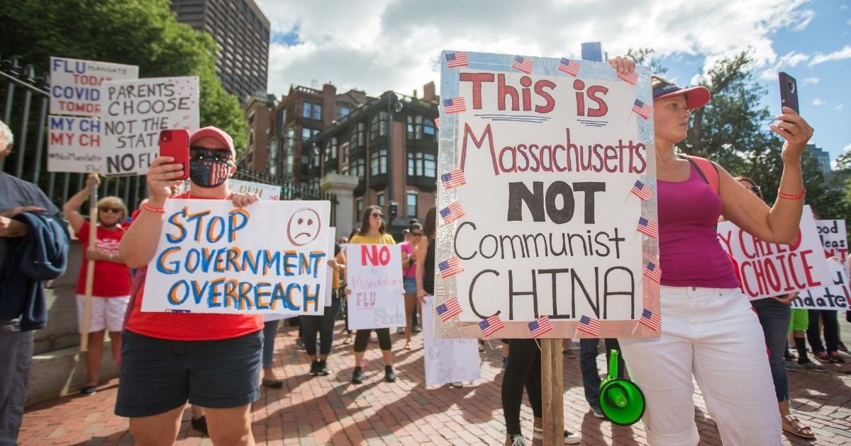 Anti-vaccine activists hold signs in front of the Massachusetts State House during a protest against Gov. Charlie Baker's mandate that all Massachusetts school students enrolled in child care, pre-school, K-12 and post-secondary institutions must receive the flu vaccine on Aug. 30, 2020, in Boston.