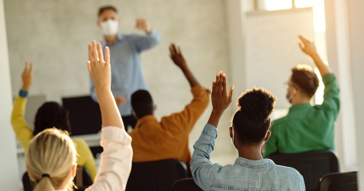 College students raise their hands to answer a question in the stock image above.