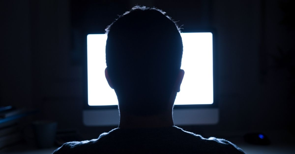 Man looking at a computer screen in the dark