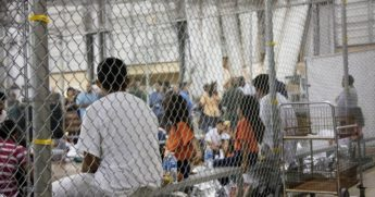 In this June 17, 2018, file photo provided by U.S. Customs and Border Protection, people who've been taken into custody related to cases of illegal entry into the United States, sit in one of the containers at a facility in McAllen, Texas.