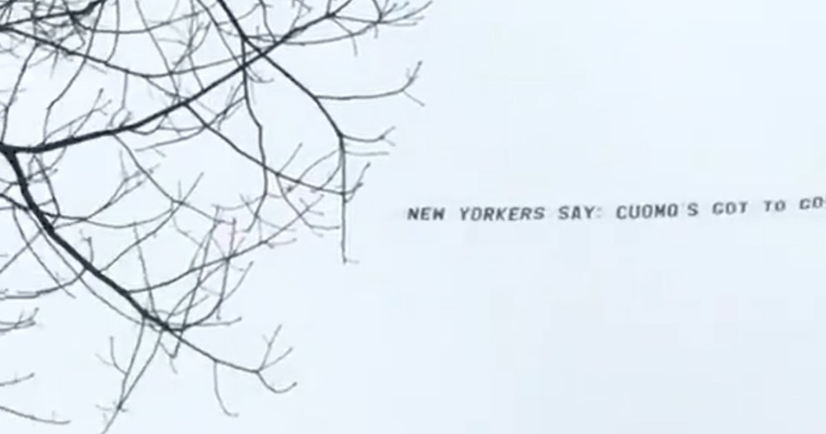 A plane flies a banner calling on New York Gov. Andrew Cuomo to resign.