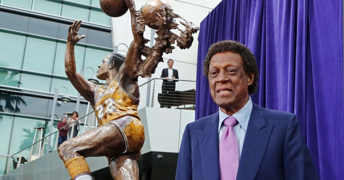 Elgin Baylor stands next to a statue, just unveiled, honoring the Minneapolis and Los Angeles Lakers great outside Staples Center in Los Angeles on April 6, 2018.