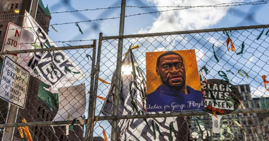 "A poster with George Floyd's picture and a sign reads that ""I Can't Breathe"" hang from a security fence outside the Hennepin County Government Center in Minneapolis on Wednesday."
