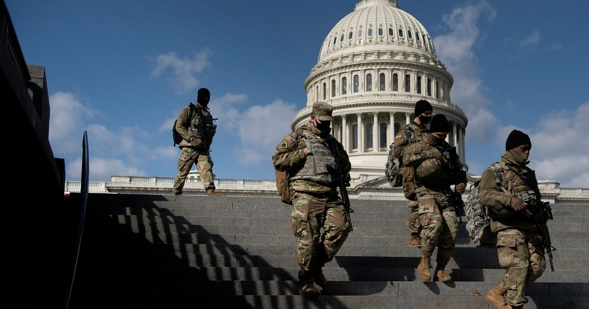 National Guard troops walk down steps outside the Capitol