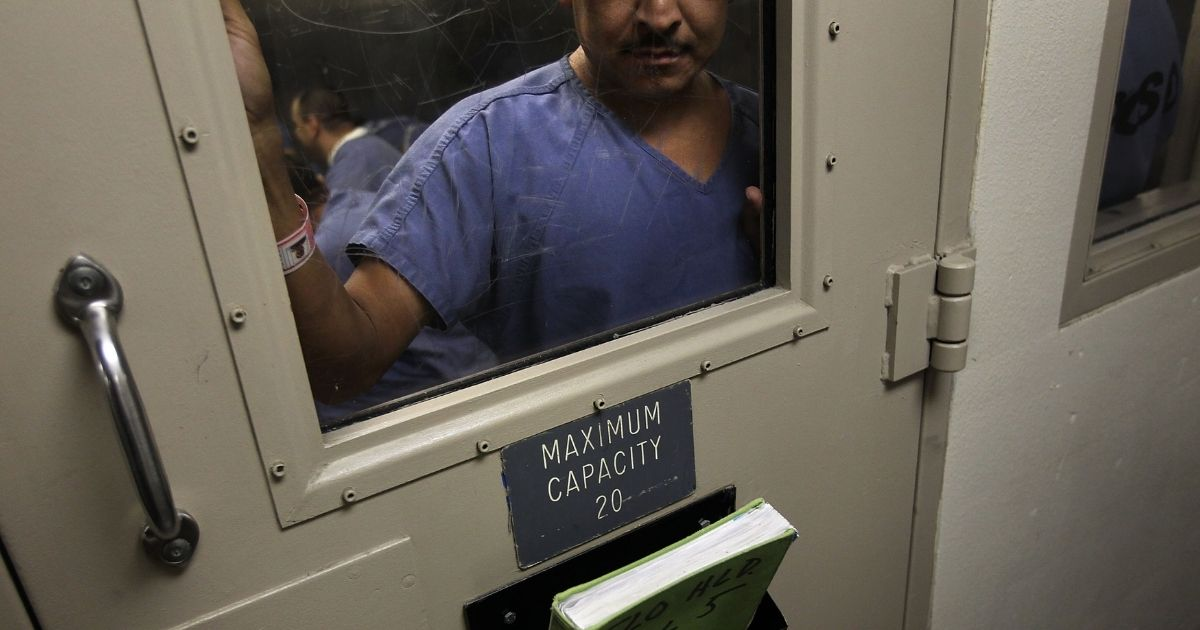 A man stands in a holding cell at the U.S. Immigration and Customs Enforcement detention facility for illegal immigrants in Florence, Arizona, on July 30, 2010.