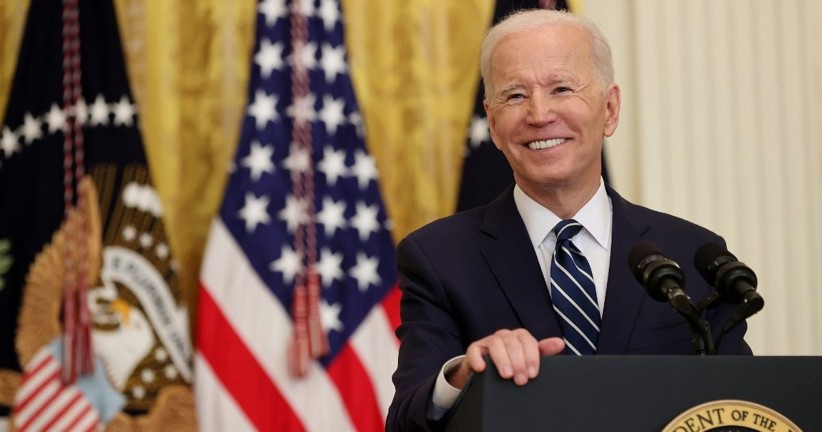 President Joe Biden smiles during the first news conference of his presidency in the East Room of the White House on Thursday in Washington, D.C.