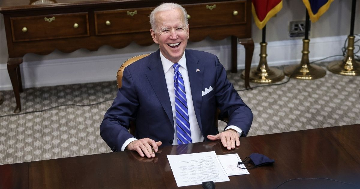 President Joe Biden smiles during a virtual call to congratulate the NASA Jet Propulsion Laboratory's Perseverance team on the successful Mars landing Thursday in the Roosevelt Room of the White House in Washington.