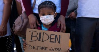 Dareli Matamoros, a girl from Honduras, holds a sign asking President Joe Biden to let her in during a migrant demonstration demanding clearer United States migration policies, at San Ysidro crossing port in Tijuana, Baja California state, Mexico on Tuesday.