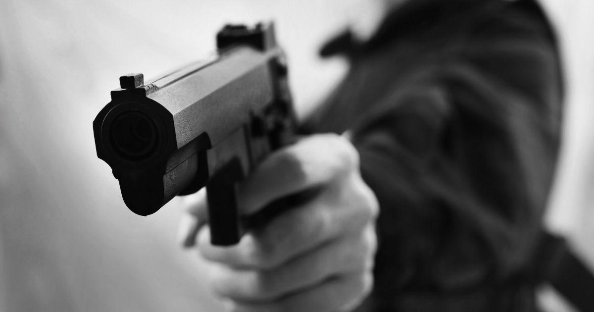 A man holds a pistol.