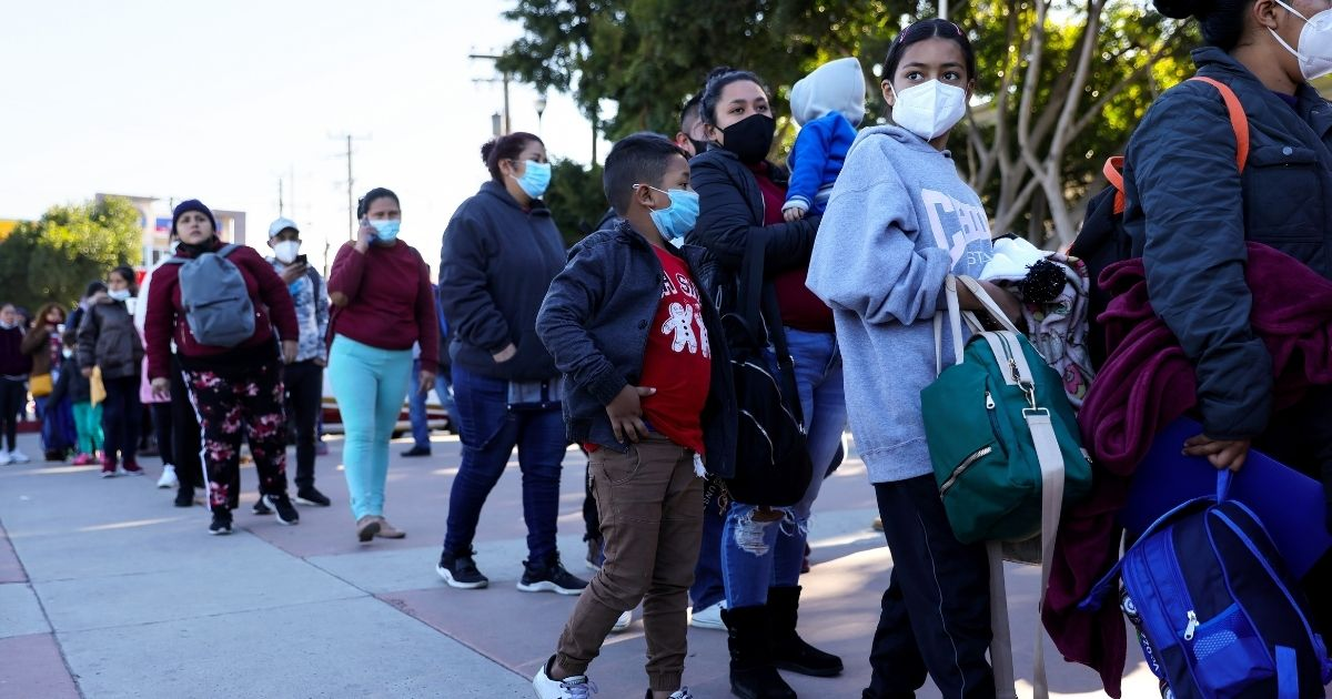 Migrants and asylum seekers wait in line for flyers explaining updated asylum policies outside the El Chaparral border crossing on Feb. 19, 2021, in Tijuana, Mexico.
