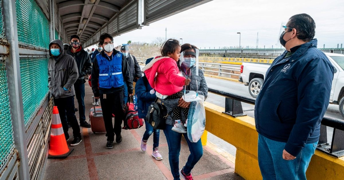 A migrant family approaches the U.S. border on Gateway International Bridge in Brownsville, Texas on March 2, 2021.