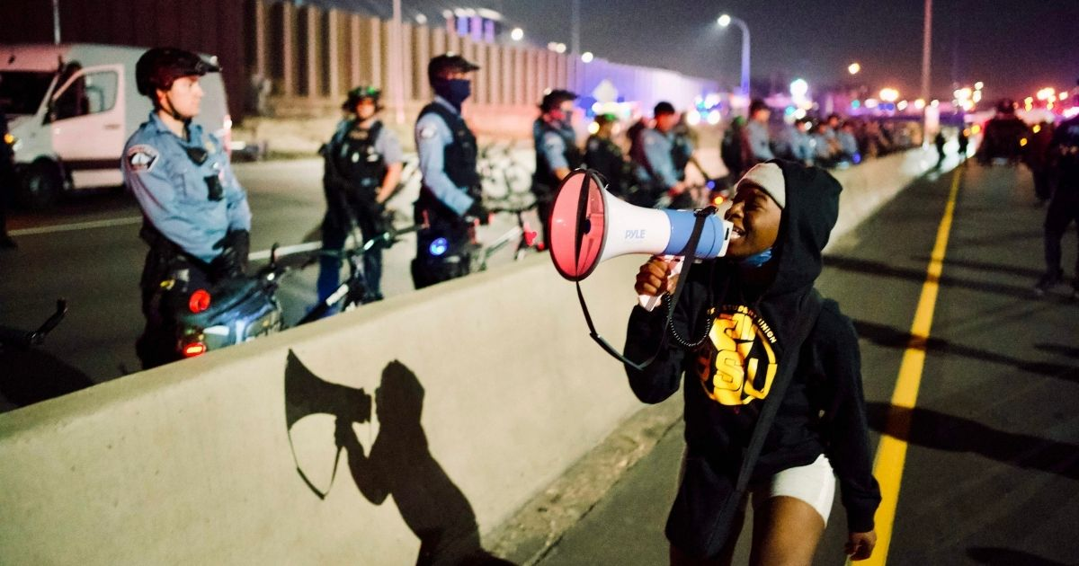 Protesters shout at police officers lined up alongside Interstate 94 in Minneapolis on Nov. 4.