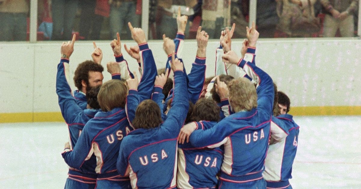 Members of the American Men's Olympic ice hockey team celebrate on the medal podium after receiving their gold medals in Lake Placid, New York, on Feb. 24, 1980.