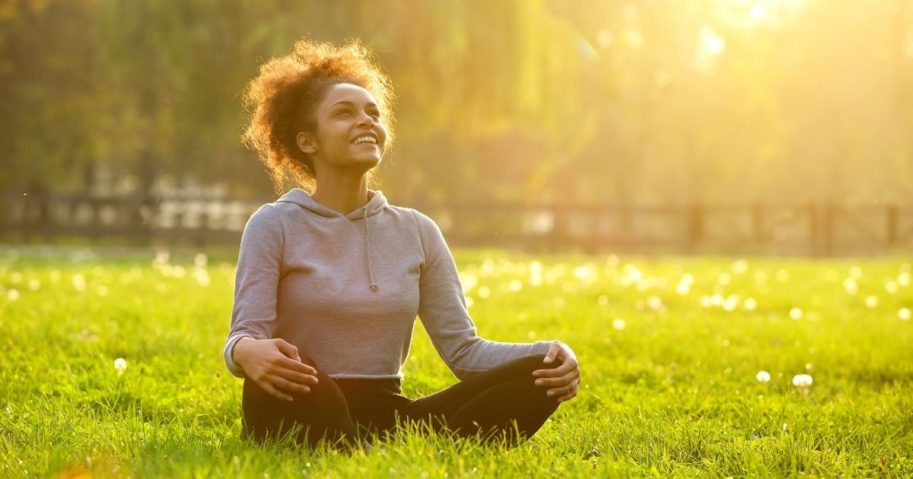 "This stock photo portrays a woman sitting in a field enjoying nature. According to Dr. Jolene Brighten, a Functional Medicine Naturopathic Physician, some of the benefits of the Fertility Awareness Method include its status as a ""non-hormonal and non-invasive approach to birth control."""
