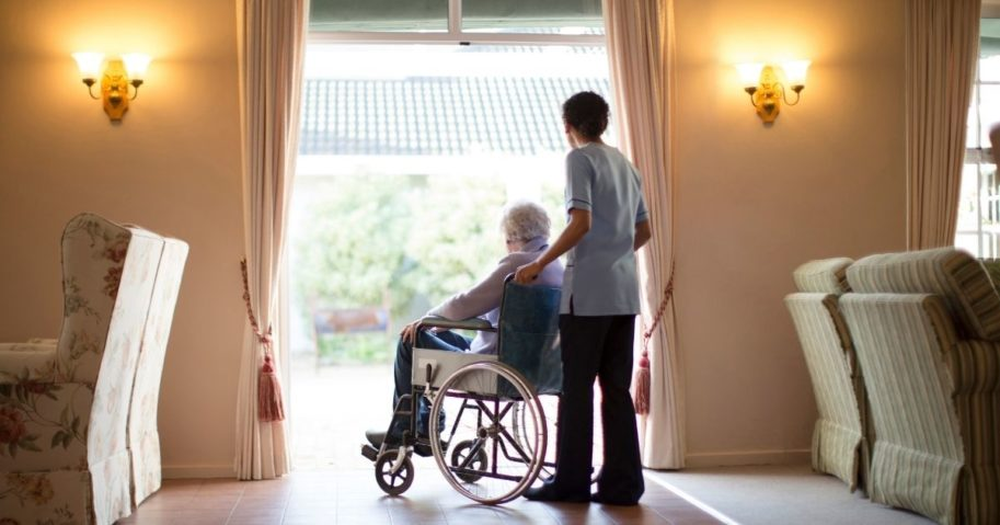 A nurse brings an elderly person in a wheelchair to a window