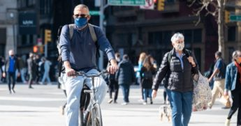 A person wearing a mask rides a bicycle in Union Square on Sunday in New York City.