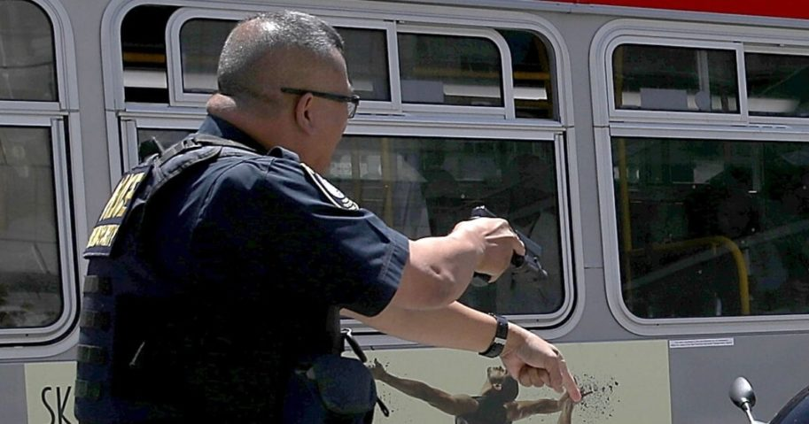 A police officer draws his gun during a confrontation with a suspect in San Francisco on June 21, 2017.