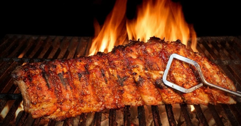 Baby back ribs cook on a flaming grill.