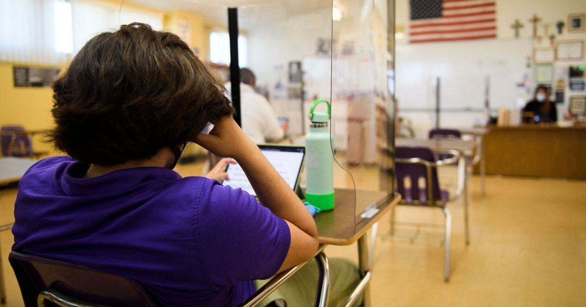 A student sitting behind a barrier works on a tablet as students return to in-person learning at St. Anthony Catholic High School during the COVID-19 pandemic on March 24, 2021, in Long Beach, California.