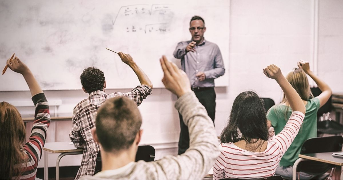 Students with their hands raised wait to be called on by the teacher in the stock image above.