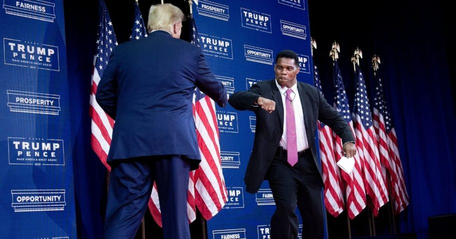 Former President Donald Trump is greeted by NFL hall of fame member Herschel Walker during an event for black supporters at the Cobb Galleria Centre on Sept. 25, 2020, in Atlanta.