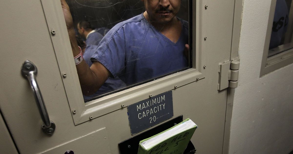 A detained migrant stands behind facility doors.