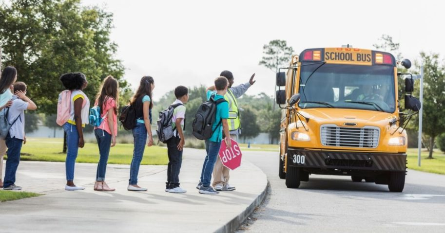 Children wait to board a schoolbus in a stock photo.