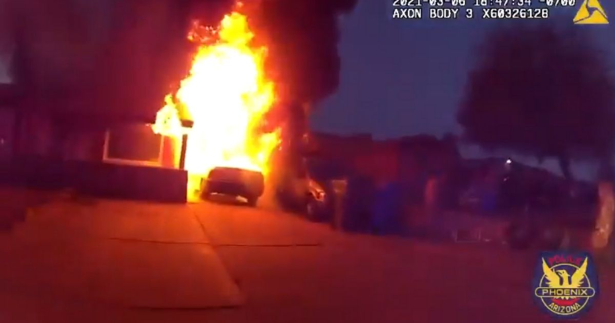 A scene of the Phoenix house on fire from the police officer's bodycam video.