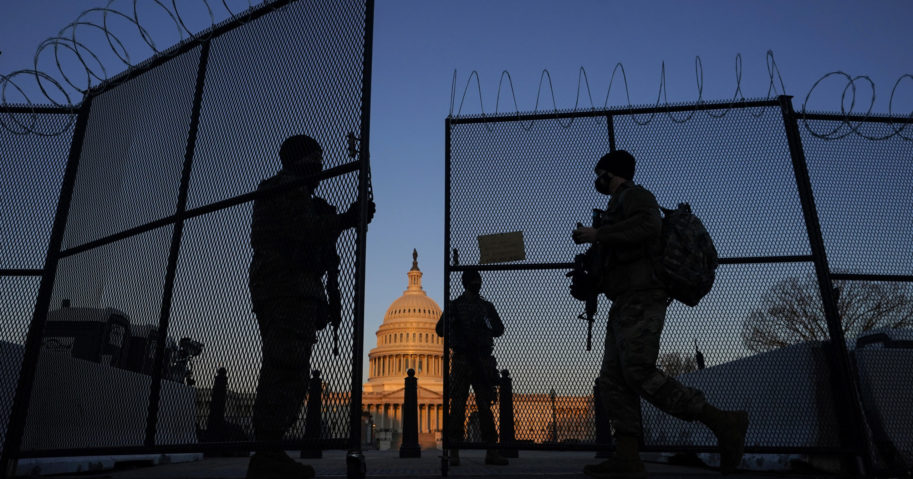 National Guard soldiers open a gate of the razor wire-topped perimeter fence around the Capitol to allow a colleague in at sunrise in Washington on March 8, 2021.