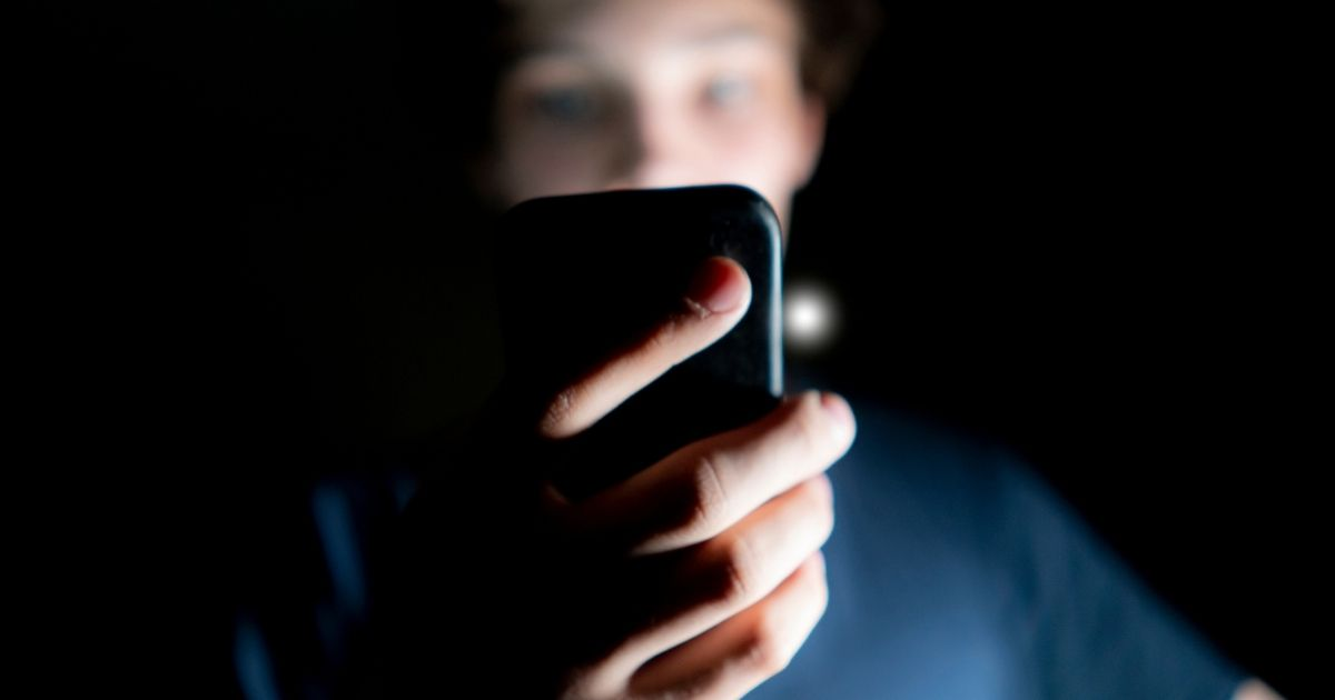 A boy looks at a smartphone in this stock image.