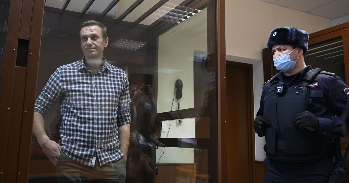 Russian opposition leader Alexei Navalny stands inside a glass cell during a court hearing at the district court in Moscow on Feb. 20, 2021.