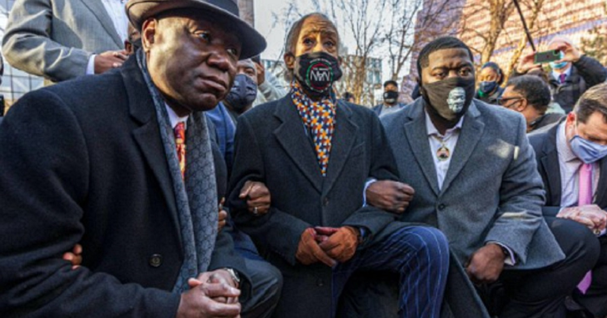 MSNBC personality Al Sharpton, flanked by attorney Benjamin Crump, left, and Pilonise Floyd, the brother of George Floyd, right, kneels outside the Minneapolis courthouse on Monday.