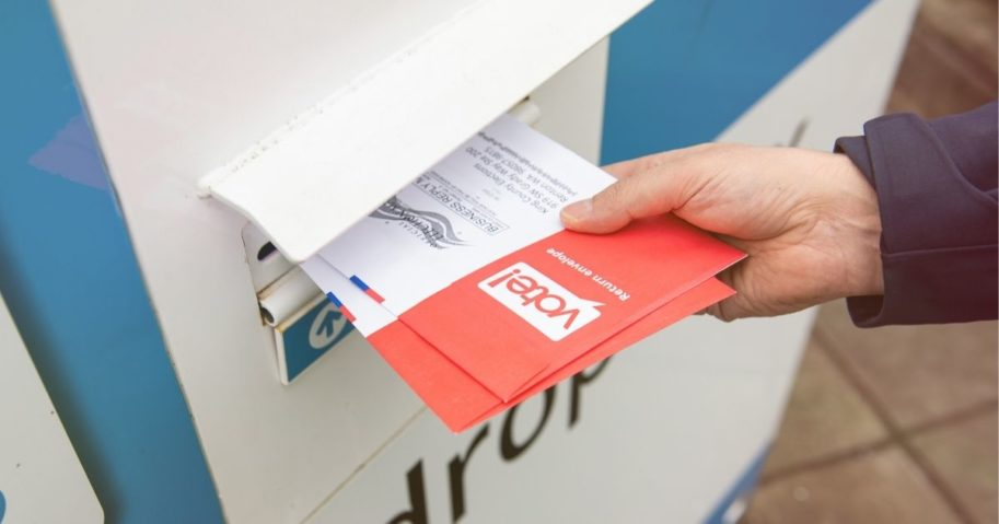 A man places a ballot in a drop box in the above stock image.