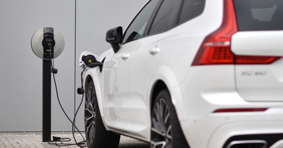 A Volvo XC60 electric car is seen plugged into a charging station outside a Volvo dealership in Reading, west of London, on March 2, 2021.