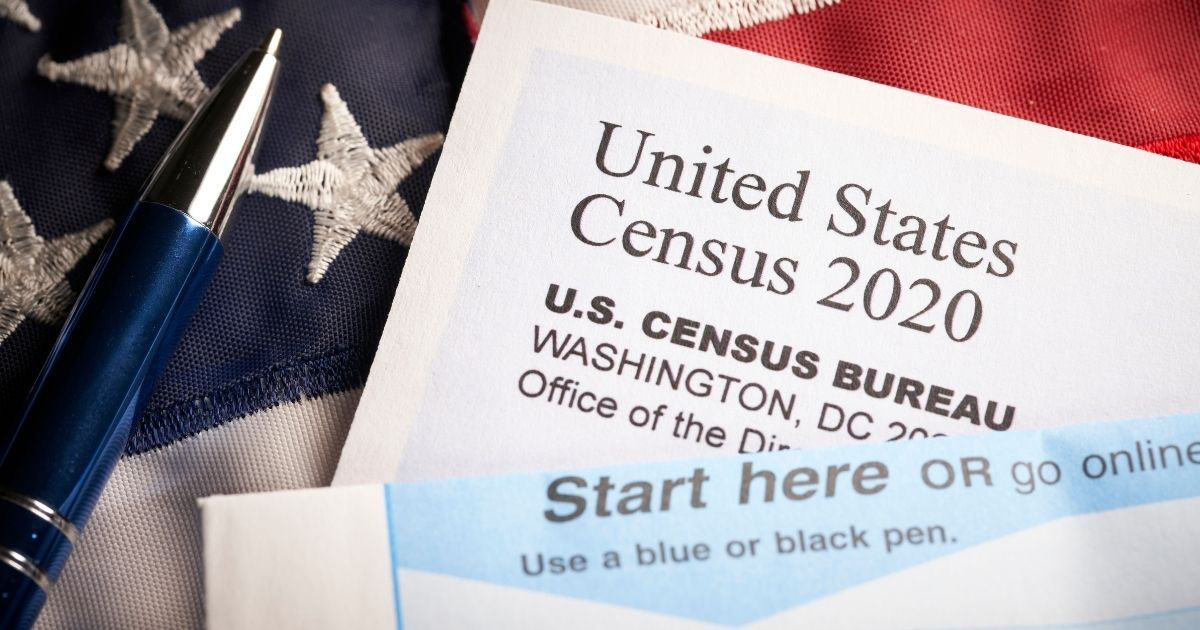 The above stock photo shows a 2020 Census survey questionnaire with an American flag.