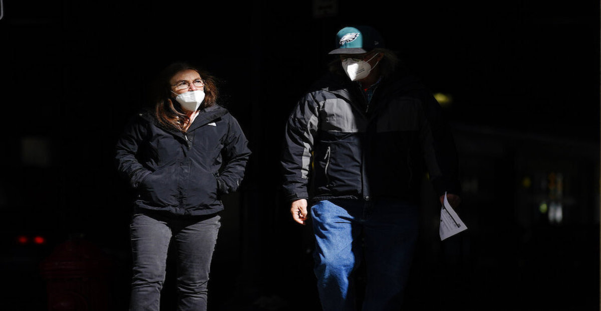 People wearing face masks as a precaution against the coronavirus walk in Philadelphia on March 3, 2021.