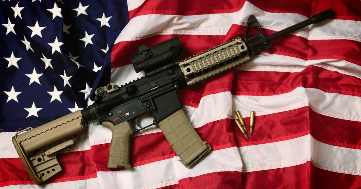 The above stock photo shows an AR-15 rifle with bullets on an American flag, a symbol of the right of patriotic Americans to bear arms, guaranteed by the Second Amendment.