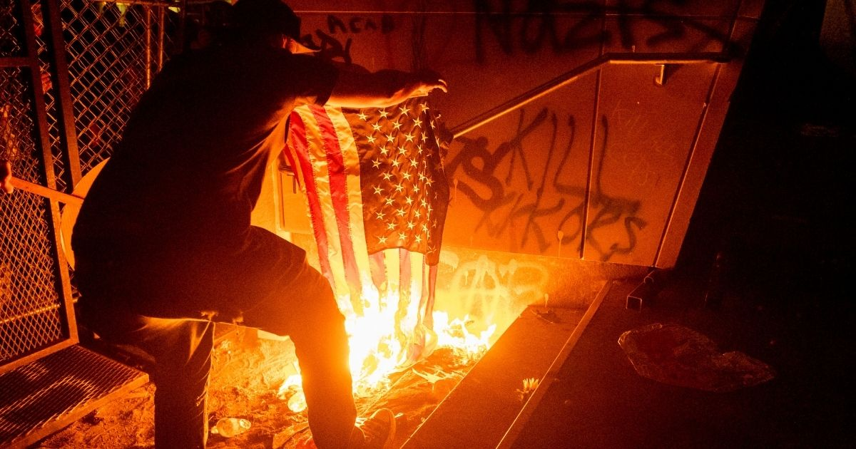 A Black Lives Matter protester burns an American flag outside the Mark O. Hatfield United States Courthouse on July 20, 2020, in Portland, Oregon.