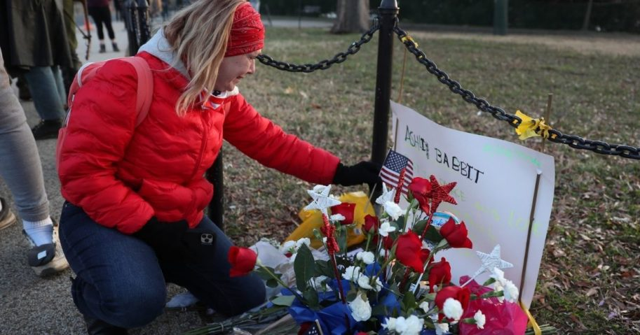 A woman becomes emotional as she visits a memorial set up near the U.S. Capitol Building for Ashli Babbitt, who was killed in the building after a pro-Trump mob broke in the day prior on Jan. 7, 2021, in Washington, D.C.