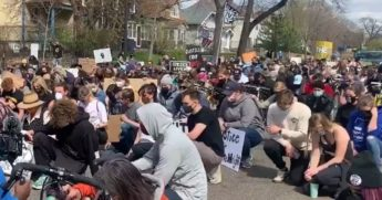 Protesters take a knee outside the Minnesota governor's mansion in St. Paul on Sunday amid reports of a shooting involving an officer in Burnsville, Minnesota.
