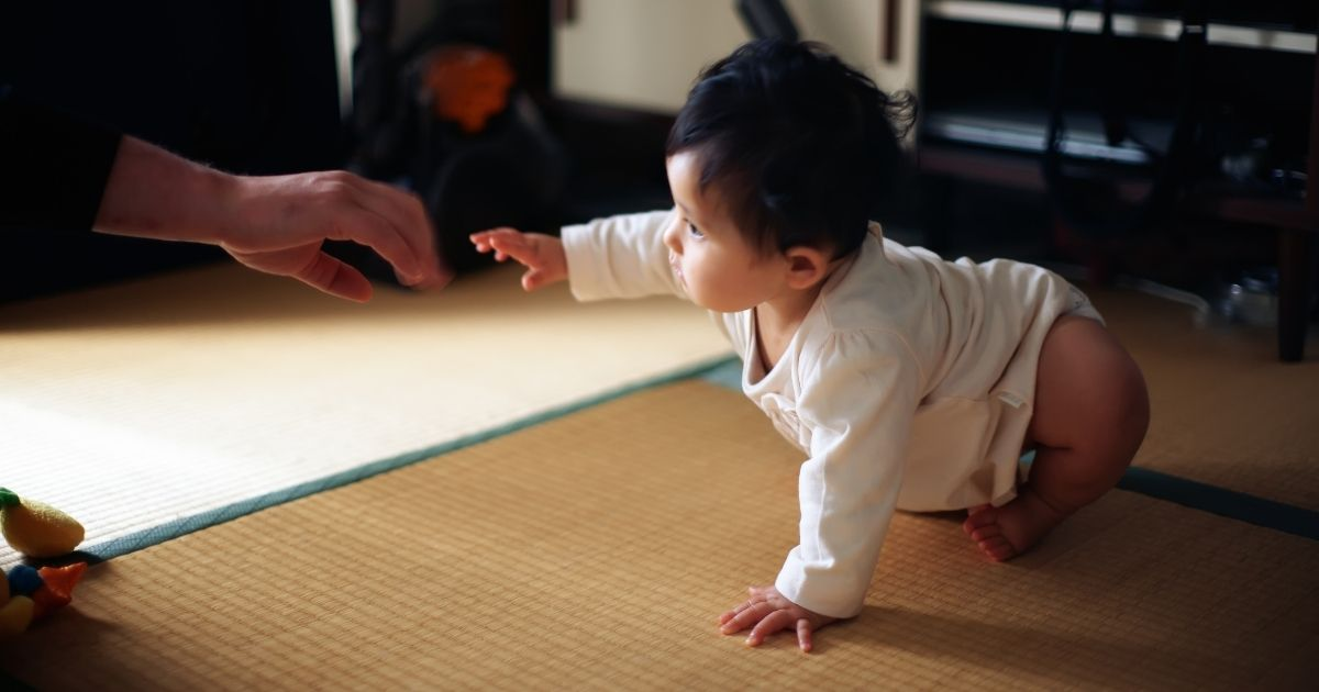 In this stock photo, a baby crawls toward an outstretched hand, ready to stand up.