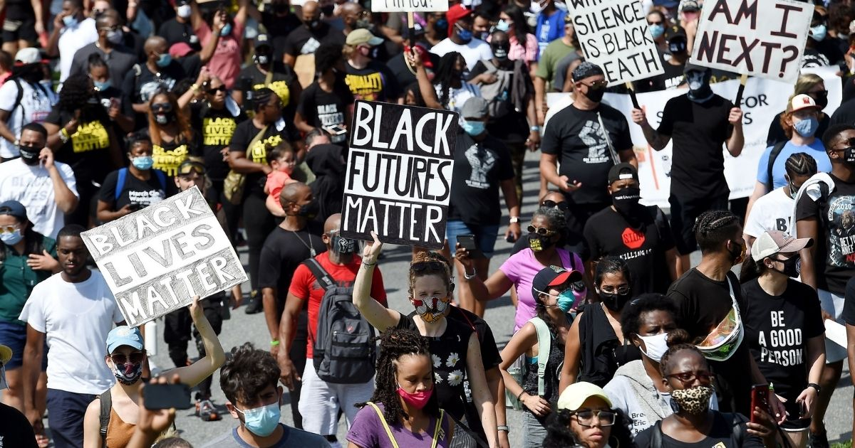 """People hold placards at the Lincoln Memorial s they attend the """"Commitment March: Get Your Knee Off Our Necks"""" protest against racism and police brutality, on Aug. 28, 2020, in Washington, D.C."""
